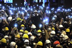In the Friday, June 21, 2019, file photo, protesters wearing yellow hardhats hold up mobile phone lights in front of police headquarters in Hong Kong, If yellow umbrellas were the iconic accessory of the 2014 protests, yellow hardhats may be this year's