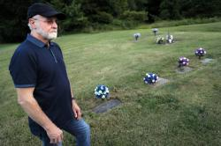 Eddie Davis stands beside the gravestone of his son Jeremy, furthest left, who died from the abuse of opioids.