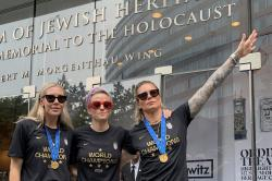In this Wednesday, July 10, 2019 photo provided by Jeff Simmons, U.S. women's soccer player Ashlyn Harris raises her left arm next to her teammates, Allie Long and Megan Rapinoe, outside the Museum of Jewish Heritage before a victory parade in New York City, to celebrate the team's Women's World Cup title