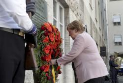 German Chancellor Angela Merkel adjusts a wreath during a memorial event at the Defence Ministry in Berlin, Germany, Saturday, July 20, 2019.