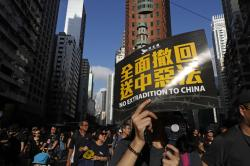 """Protesters march with a card that reads """"Fully withdraw the extradition to China evil law"""" in Hong Kong on Sunday, July 21, 2019."""