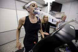 In this April 23, 2019 photo, research scientist Leila Walker, left, is assisted by nutritional physiologist Holly McClung, center, as they demonstrate equipment designed to evaluate fitness levels in female soldiers