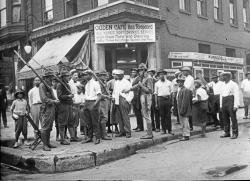 In this 1919 photo provided by Chicago History Museum, a crowd of men and armed National Guard stand in front of the Ogden Cafe during race riots in Chicago