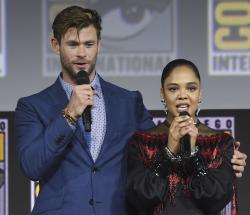 """Chris Hemsworth, left, and Tessa Thompson speak during the """"Thor Love And Thunder"""" portion of the Marvel Studios panel on day three of Comic-Con International in San Diego."""