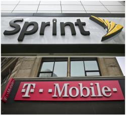 This combination of April 30, 2018, file photos shows signage for a Sprint store in New York's Herald Square, top, and signage at a T-Mobile store in New York