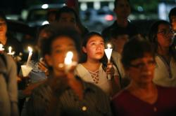 People attend a candlelight vigil for victims of a mass shooting at a shopping complex in El Paso, Texas.