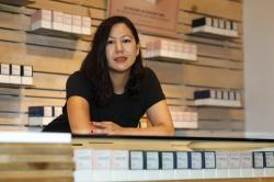 In this Friday, July 26, 2019 photo, Leslie Siu poses for a portrait next to her cannabis products geared toward women on display in Groundswell dispensary in east Denver