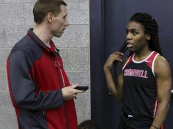 Cromwell High School track coach Brian Calhoun, left, speaks to transgender athlete Andraya Yearwood during a break at a meet at Hillhouse High School in New Haven, Conn.