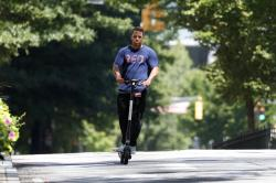 A man rides a electric scooter Thursday, Aug. 8, 2019, in Atlanta