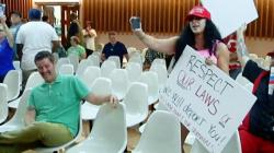 "This photo from video provided by KVOA-TV shows Alex Kack, in the green shirt at left, laughing at a protester during a vote to put a ""sanctuary city"" initiative on the November ballot during a meeting of the Tucson, Ariz., City Council Tuesday, Aug. 6"