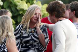 Mourners console each other after a mass in the chapel on the campus of Saint Francis University to celebrate the life of Nicholas Cumer.