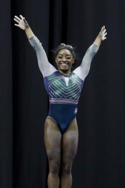 Simone Biles celebrates after competing on the beam at the U.S. Gymnastics Championships on Friday, Aug. 9, 2019, in Kansas City, Mo. (AP Photo/Charlie Riedel)