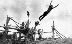 In this Aug. 15, 1969 photo, rock music fans sit on a tree sculpture as one leaps mid-air onto a pile of hay during the Woodstock Music and Art Festival held in Bethel, N.Y. (AP)