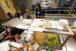 A teacher lines up the students for school-prepared lunches at Madison Crossing Elementary School.