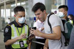 An airport security officer checks on a traveller's flight information at the airport main entrance gate in Hong Kong, Wednesday, Aug. 14, 2019.