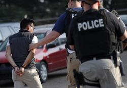 In this Aug. 7, 2019, file photo, a man is taken into custody at a Koch Foods Inc. plant in Morton, Miss.