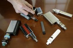 In this Tuesday, April 10, 2018 photo, a high school principal displays vaping devices that were confiscated from students at the school in Massachusetts