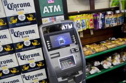 In this April 18, 2018, file photo, an ATM machine is in use at a New York convenience store