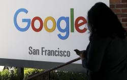 In this May 1, 2019, file photo, a person walks past a Google sign in San Francisco