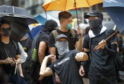 A protester prepares to throw an egg at a pro-government lawmaker during a march in Hong Kong Saturday, Aug. 17, 2019.