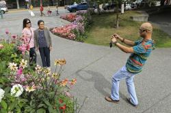 Junar Lim takes photos of Ziah Lim, left, and Arsenia Lim, all of Cavite, the Philippines, at gardens in Town Square in Anchorage, Alaska, Thursday, Aug. 15, 2019.