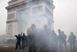 In this Saturday, Jan. 12, 2019 file photo riot police take position around the Arc de Triomphe during clashes with yellow vest protesters, in Paris, France. (AP Photo/Thibault Camus, File)