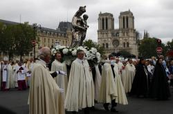 Catholic clergymen and pilgrims take part in an emotional procession with the statue of the Virgin Mary rescued from the April blaze past the fire-ravaged Notre Dame Cathedral to celebrate the Assumption of the Virgin in Paris, Thursday, Aug. 15, 2019