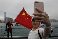 In this Saturday, Aug. 17, 2019 file photo, pro-China supporters take a selfie with a Chinese national flag to support police and anti-violence during a rally at a park in Hong Kong