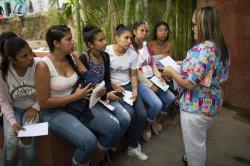 In this photo taken July 25, 2019, women listen to a nurse before getting hormonal implants to prevent pregnancies at a clinic in the impoverished Caucaguita neighborhood on the outskirts of Caracas, Venezuela