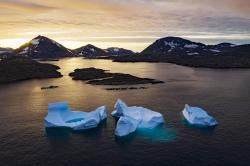 In this Aug. 16, 2019, photo, large Icebergs float away as the sun rises near Kulusuk, Greenland