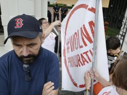 Protesters with banners calling on Justice Minister Zbigniew Ziobro to quit over allegations that his deputy encouraged an online hate campaign against defiant judges in Warsaw, Poland, Wednesday, Aug. 21, 2019