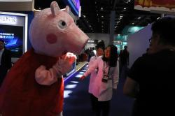 A woman reacts to a Peppa Pig mascot during the Global Mobile Internet Conference (GMIC) in Beijing, China.