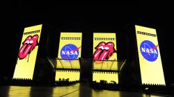 The logos for the band The Rolling Stones and NASA are displayed side-by-side on video monitors onstage before the Rolling Stones' concert at the Rose Bowl, Thursday, Aug. 22, 2019, in Pasadena, Calif.