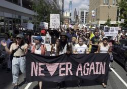 In this July 4, 2019, file photo, protesters assembled by a majority Jewish group called Never Again Is Now walk through traffic as they make their way to Independence Mall in Philadelphia