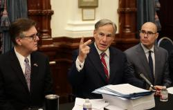 Texas Gov. Greg Abbott, center with Speaker of the House Dennis Bonnen, right, and Lt. Governor Dan Patrick, left, makes opening statements during a round table discussion, Thursday, Aug. 22, 2019, in Austin, Texas