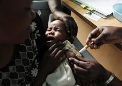 In this Oct. 30, 2009 file photo, a mother holds her baby receiving a new malaria vaccine as part of a trial at the Walter Reed Project Research Center in Kombewa in Western Kenya