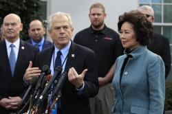 In this March 4, 2019, file photo, White House trade adviser Peter Navarro, front left, with Transportation Secretary Elaine Chao, right, and U.S. Maritime Administration Administrator Mark Buzby, back left, speaks to reporters outside the West Wing of the White House in Washington