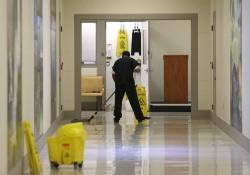 In this June 21, 2017, file photo, a detainee mops a floor in a hallway of the Northwest Detention Center in Tacoma, Wash., during a media tour of the facility