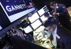 In this Aug. 5, 2014, file photo, specialist Michael Cacace, foreground right, works at the post that handles Gannett on the floor of the New York Stock Exchange