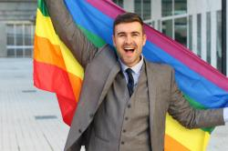 This stock photo shows a man in a business suit holding a Pride flag