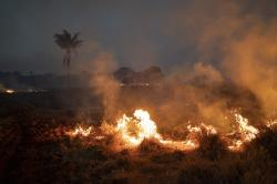 A fire burns a field on a farm in the Nova Santa Helena municipality, in the state of Mato Grosso, Brazil, Friday, Aug. 23, 2019