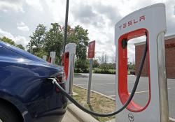 In this July 19, 2019 file photo, a Tesla vehicle charges at a Tesla Supercharger site in Charlotte, N.C.