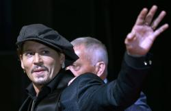 Johnny Depp waves for fans upon his arrival at a film premier in Tokyo.