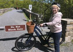In this June 8, 2019 file photo, Janice Goodwin stands by her electric-assist bicycle at a gate near the start of the carriage path system where bikes such as her are banned inside Acadia National Park, in this photo June 8, 2018, in Bar Harbor, Maine