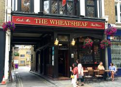 Tourists pass the Wheatsheaf pub in London.