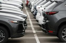 In this Sunday, May 19, 2019, file photo lines of unsold vehicles sit at a dealership in Littleton, Colo.
