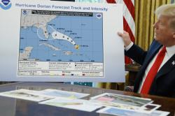 President Donald Trump holds a chart as he talks with reporters after receiving a briefing on Hurricane Dorian in the Oval Office of the White House, Wednesday, Sept. 4, 2019, in Washington