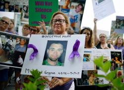 In this Friday, Aug. 17, 2018, file photo, Christine Gagnon of Southington, Conn., protests with other family and friends who have lost loved ones to OxyContin and opioid overdoses at Purdue Pharma LLP headquarters in Stamford, Conn.