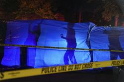 Police put up a blue tarp to block the view of a body at the scene of an officer involved shooting on East 77th Street in Richfield, Minn., Saturday night, Sept. 7, 2019