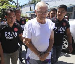 In this Feb. 19, 2019 photo, Philippine National Police, National Capital Region Police Office (NCRPO) agents escort Catholic priest Father Pius Hendricks to be served five additional arrest warrants at the Regional Special Operations Unit at Camp Bagong Diwa in suburban Taguig, east of Manila, Philippines